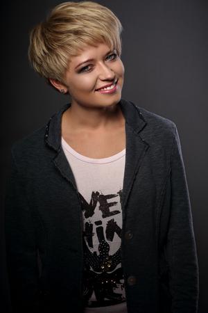 Gelukkige toothy glimlachende jonge blonde vrouw die met de korte stijl van het loodjeshaar in grijs in jasje op donkere achtergrond kijken. Closeup portret