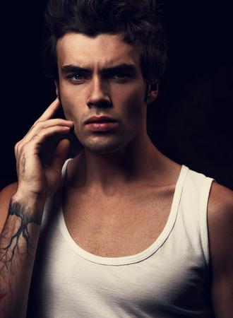 Sexy starker junger gutaussehender Mann, der im weißen T-Shirt mit der Hand nahe dem Gesicht auf drak Schattenhintergrund aufwirft. Nahaufnahmeportrait. Getönten