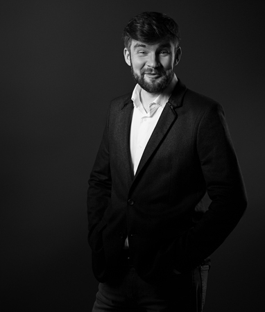 Emotion enjoying handsome beard male posing in fashion suit and white style shirt looking on dark grey shadow background. Black and white portrait