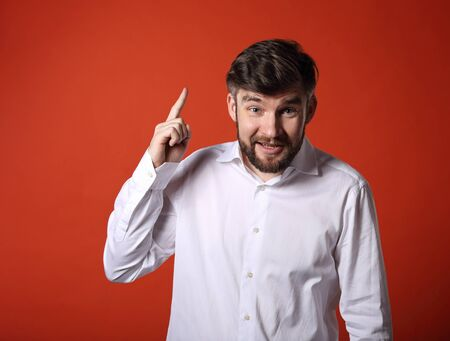 Fun emotional bearded smiling man thinking and have an idea holding and showing the finder up on empty copy space orange background Stock fotó