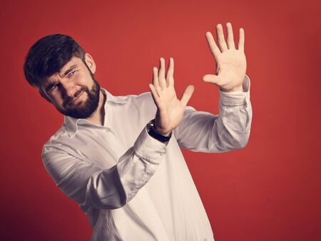 Stressed unhappy frightened bearded business man defends himself the hands in white shirt on bright orange background. Closeup toned portrait