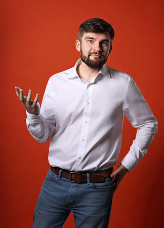 Skeptic annoyed young bearded business man gesturing in white shirt on bright orange background