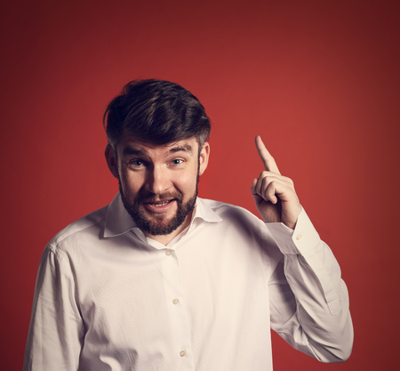 Fun emotional bearded smiling man thinking and have an idea holding and showing the finder up red background. Closeup portrait