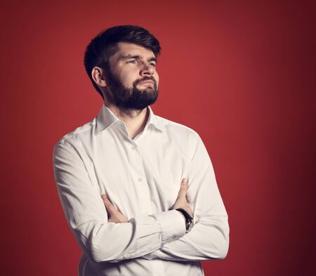 Serious thinking bearded business man posing in fashion white style shirt looking up on red background. Closeup toned portrait
