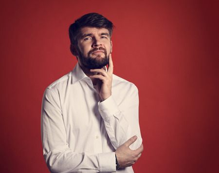 Thinking bearded charismatic man in whirt shirt looking on red background with empty copy space. Closeup portrait