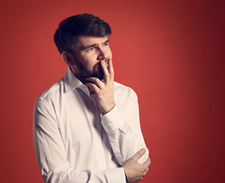Thinking bearded charismatic man in whirt shirt looking on dark red background with empty copy space. Closeup toned portrait Stock Photo