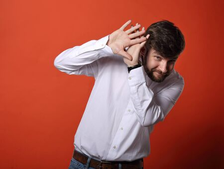 Stressed unhappy frightened bearded business man defends himself the hands in white shirt on bright orange background Stock Photo