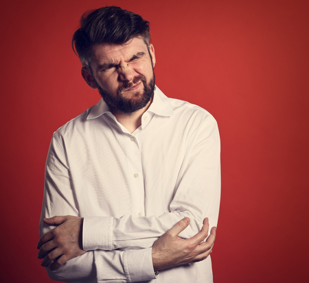 Grimacing unhappy bearded business man with closed eyes holding the hands his abdomen with pain in white style shirt. Closeup portrait on red background with empty copy space Stock Photo