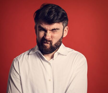 Grimacing emotional disgasted bearded business man looking unhappy in white style shirt. Closeup portrait on red background. Closeup toned portrait