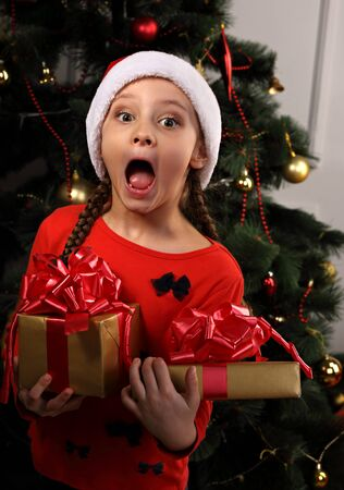Cute excited surprising kid girl with open mouth in Christmas santa claus hat holding the red boxes with gift with very expression face on green fur tree background. Closeup portrait