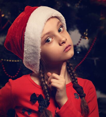 Cute kid girl with in Christmas santa claus hat thinking about new year gift and holding the finger under the face on green fur tree background. Closeup toned portrait
