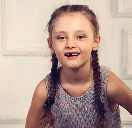 Fun emotional kid girl without milk tooth posing in fashion blouse and braid hairstyle in studio wall background. Closeup toned portrait Stock Photo