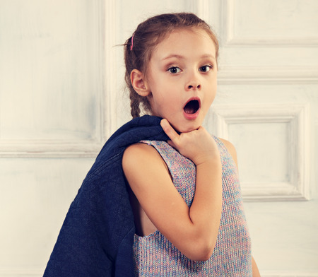 Surprising kid girl with opened mouth looking and holding blue jacket. Closeup toned portrait 스톡 콘텐츠