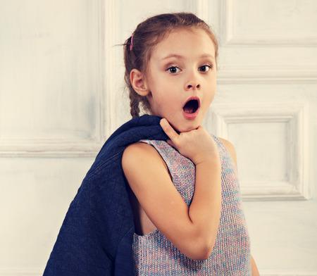 Verrassend kind meisje met geopende mond op zoek en blauwe jas te houden. Close-up afgezwakt portret Stockfoto