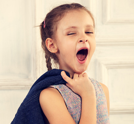 Kid girl in fashion blouse posing in studio and wanting to sleep and yawning 스톡 콘텐츠
