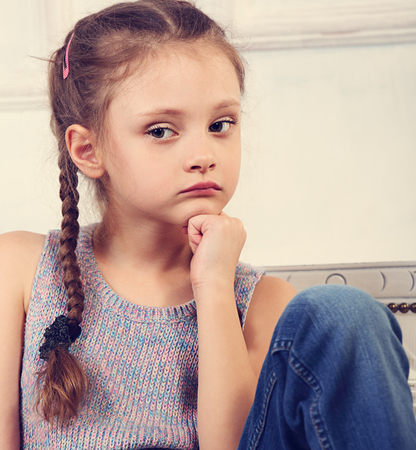 Beautiful thinking serious cute kid girl sitting on the bench in blue jeans and looking sad. Closeup portrait Stok Fotoğraf
