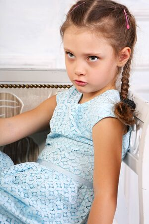 Angry thinking kid girl sitting on the bench in blue dress and looking up. Studio portrait. Closeup Stock Photo