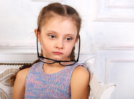 Sad thinking calm kid girl in eyeglasses looking. Closeup studio portrait Stok Fotoğraf