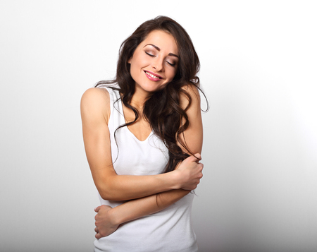Happy sporty woman hugging herself with natural emotional enjoying face on white background. Love concept of yourself body