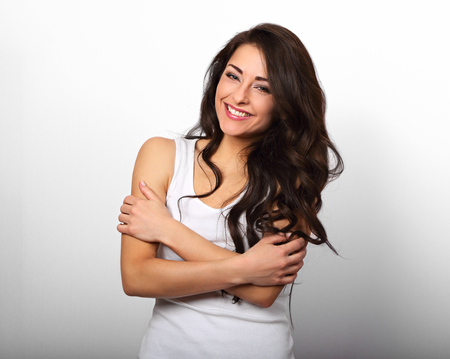 Happy smiling beautiful woman hugging herself with natural emotional enjoying face on white background. Love concept