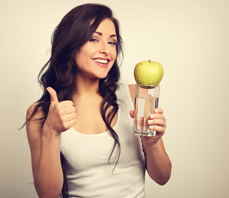 Happy healthy woman holding apple and clear water in hand, showing thumb up and looking with toothy smiling. Toned vintage portrait
