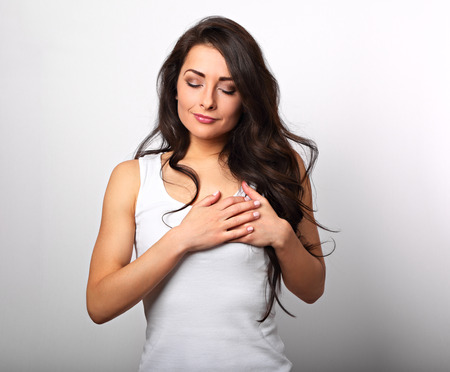Beautiful woman in love holding herself chest and heart two hands with enjoying smiling face and thinking about emotion relationship on white background Banque d'images