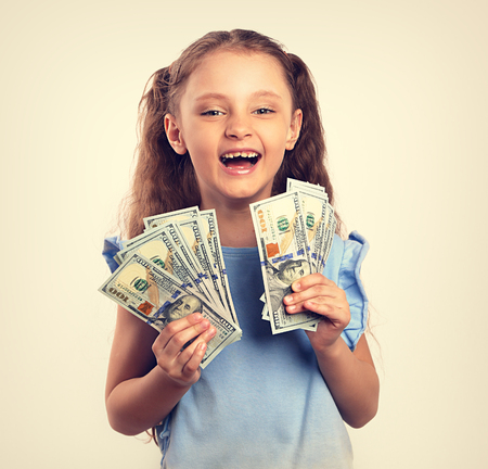 Happy laughing rich kid girl holding money in the hand. Vintage toned portrait Stock Photo - 100399960