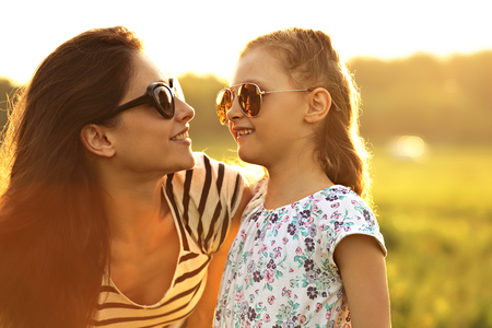 Happy fashion kid girl and her mother in trendy sunglasses looking on each other on nature sunset background. Closeup portrait of happiness.