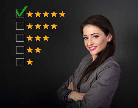 Beautiful business woman in grey suit looking happy with folded arms on dark grey background. The best rating, evaluation, online rewiew. Confident happy woman voting to five yellow star to increase ranking