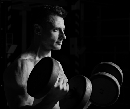 Handsome strong brutal man doing the exercises with dumbbells on dark shadow background. Profile view. Closeup portrait. Black and white Stock Photo