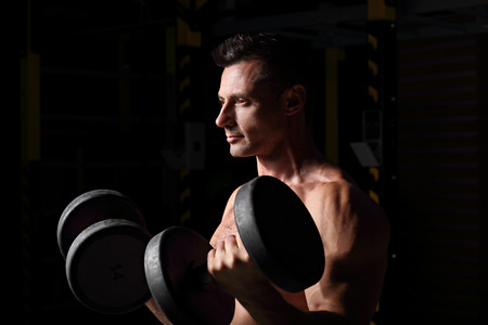 Handsome strong brutal man doing the exercises with dumbbells on dark shadow background. Profile view. Closeup portrait Stock Photo