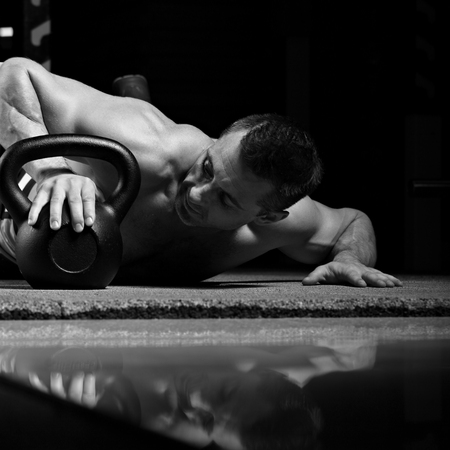 Handsome happy brutal man lying, hugging and looking on the kettlebell on dark sport club background. Fun concept of love to sport life. Black and white closeup portrait