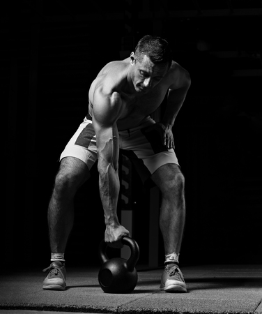 Handsome strong brutal man lifting one muscle arm the kettlebell on dark sport club background. Training in light gym in art shadow. Black and white