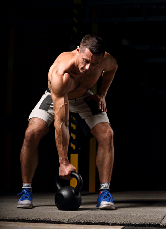 Handsome strong brutal man lifting one muscle arm the kettlebell on dark sport club background. Training in light gym in art shadow. Reklamní fotografie
