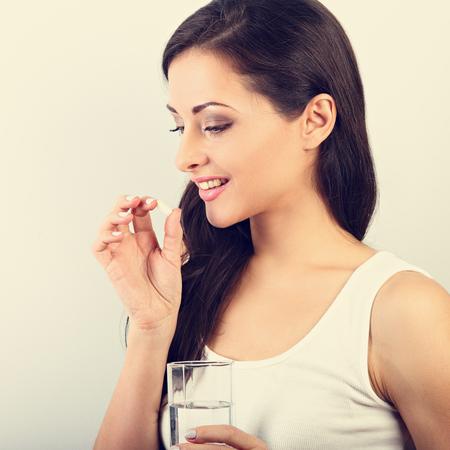 Donna positiva sorridente felice che mangia la pillola e che tiene il bicchiere d'acqua in mano su sfondo bianco. Ritratto di vista di profilo del primo piano. tonico