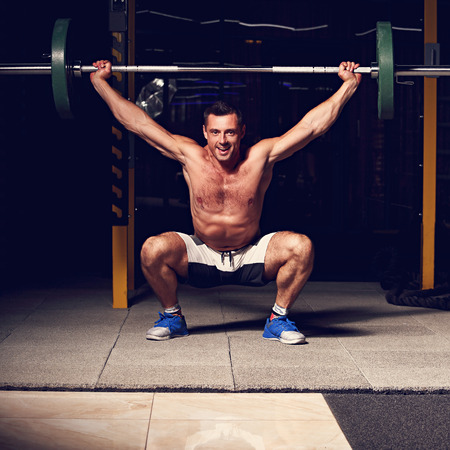 Handsome smiling brutal man lifting barbell in crossfit gym on dark sport club background with shadows. Low section of dedicated. Toned vintage portrait