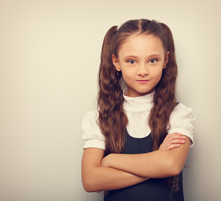 Fun pupil school girl with long hair style in uniform looking serious with folded arms on empty copy space background. Toned vintage portrait Imagens
