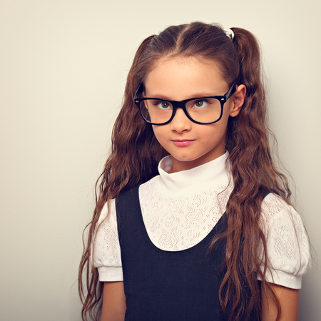 Grimacing  pupil girl with long hair style in fashion eyeglasses in uniform squint eyes on blue background with empty copy space. Toned vintage portrait