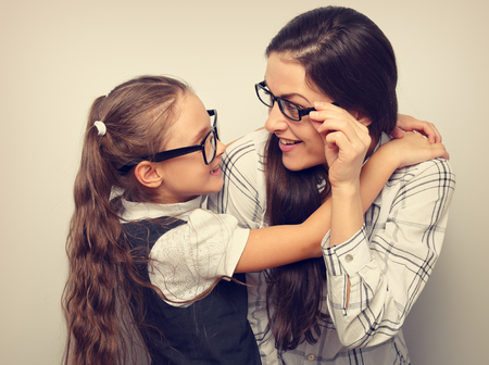 Happy surprising mother and excite kid in fashion glasses looking each other and cuddling on empty copy space blue background.