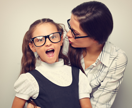 Happy mother whispering the secret to her excite kid in fashion glasses with opened mouth on empty copy space background. Toned vintage portrait