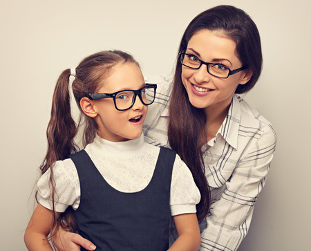 Happy young mother and lauging kid in fashion glasses hugging on empty copy space background. Toned vintage portrait
