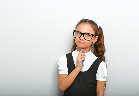 Thinking serious skeptical pupil girl in fashion eyeglasses with in school uniform with pencile inder the face on blue background with copy empty space
