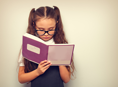 Smart pupil kid girl in eyeglasses looking in the textbook and dooing the exercices on toned color background. Vintage Standard-Bild