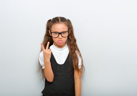 Grimacing  pupil girl with long hair style in fashion eyeglasses in uniform showing victory sign and tongue on blue background with empty copy space. Stock Photo