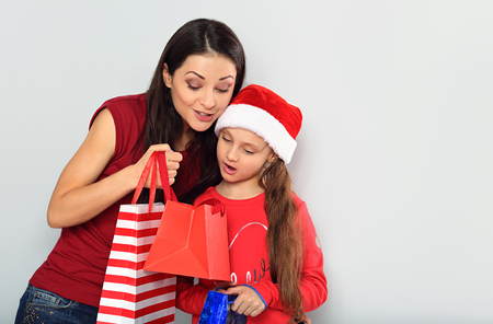 Happy surprising mother and cute daughter in santa clause hat opening the Christmas presents in package with excited face on blue studio background