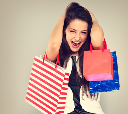Excited surprising shouting woman with opened mouth in fashion white dress with shopping bags. Happy New Year Holidays sales on toned vintage background Фото со стока