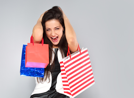 Excited surprising shouting woman in fashion white dress with shopping bags. Happy New Year Holidays sales on blue background