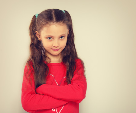 Abandoned kid girl in red Christmas blouse looking with double emotions, smiling and sad with folded arms. Toned portrait