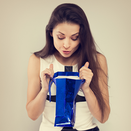 Excited surprising woman looking in gift blue bag with smiling on blue background. Happy holidays. Toned closeup portrait Foto de archivo