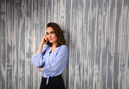 Beautiful positive young happy woman with hand under the face thinking and looking in casual blue shirt and short hair stye on blue background